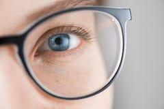 Κλείστε αυξημένος της γυναίκας με τα μπλε μάτια με τα γυαλιά στοκ εικόνες