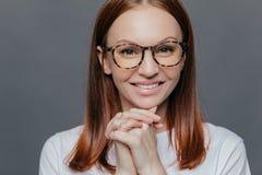 Κλείστε αυξημένος της ευτυχούς νέας Ευρωπαίας γυναίκας έχει το ευχάριστο χαμόγελο, κρατά τα χέρια μαζί κοντά στο πηγούνι, φορά τα στοκ εικόνες με δικαίωμα ελεύθερης χρήσης