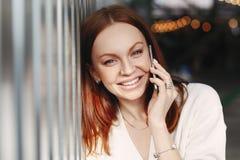 Κλείστε αυξημένος της εύθυμης γυναίκας με την καφετιά τρίχα, έχει τη φιλική κινητή συνομιλία, πρέπει να αποτελέσει, οδοντωτό χαμό στοκ φωτογραφίες