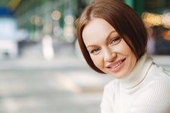 Κλείστε αυξημένος της ικανοποιημένης Ευρωπαίας γυναίκας με την εύθυμη έκφραση, που ντύνεται στα περιστασιακά ενδύματα, εξετάζει μ στοκ εικόνα με δικαίωμα ελεύθερης χρήσης