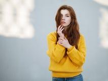 Κλείστε αυξημένος της μυθικής redhead γυναίκας με μακρυμάλλη στο κίτρινο πουλόβερ που έχει τη διασκέδαση στο γκρίζο υπόβαθρο συμπ στοκ φωτογραφίες
