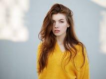 Κλείστε αυξημένος της μυθικής redhead γυναίκας με μακρυμάλλη στο κίτρινο πουλόβερ που έχει τη διασκέδαση στο γκρίζο υπόβαθρο συμπ στοκ εικόνα με δικαίωμα ελεύθερης χρήσης