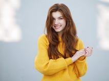 Κλείστε αυξημένος της μυθικής redhead γυναίκας με μακρυμάλλη στο κίτρινο πουλόβερ που έχει τη διασκέδαση στο γκρίζο υπόβαθρο συμπ στοκ εικόνες με δικαίωμα ελεύθερης χρήσης
