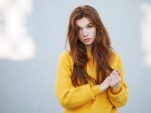 Κλείστε αυξημένος της μυθικής redhead γυναίκας με μακρυμάλλη στο κίτρινο πουλόβερ που έχει τη διασκέδαση στο γκρίζο υπόβαθρο συμπ στοκ εικόνες