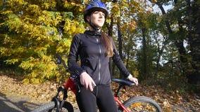 Κλείστε αυξημένος της νέας γυναίκας σε ένα ποδήλατο στο πάρκο φθινοπώρου κίνηση αργή απόθεμα βίντεο