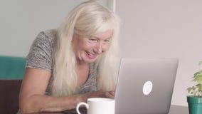 Κλείστε αυξημένος της συνταξιούχου γιαγιάς ηλικιωμένων γυναικών χρησιμοποιώντας το lap-top στο σπίτι στο καθιστικό Ευτυχής ηλικιω απόθεμα βίντεο