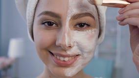 Κλείστε αυξημένος της όμορφης νέας γυναίκας που εφαρμόζει τη μάσκα στο πρόσωπο φιλμ μικρού μήκους