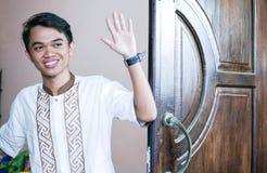Κλείστε αυξημένος του ατόμου καλωσόριζε το φίλο του μπροστά από την πόρτα με ένα κύμα των χεριών στοκ εικόνα με δικαίωμα ελεύθερης χρήσης