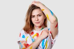 Κλείστε αυξημένος του ελκυστικού νέου θηλυκού καλλιτέχνη, έχει λεκιάσει τα ενδύματα με τα χρώματα μετά από να κάνει τα ζωηρόχρωμα στοκ εικόνα με δικαίωμα ελεύθερης χρήσης