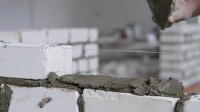 Κλείστε αυξημένος του εργάτη οικοδομών που βάζει τα άσπρα τούβλα για τον τοίχο φιλμ μικρού μήκους