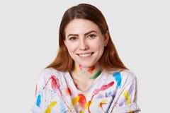 Κλείστε αυξημένος του ευτυχούς χαμογελώντας ταλαντούχου ζωγράφου έχει τη σκοτεινή ευθεία τρίχα, ίχνη χρωμάτων στα ενδύματα, λαμβά στοκ φωτογραφία με δικαίωμα ελεύθερης χρήσης