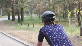 Κλείστε αυξημένος του θηλυκού οδηγώντας ποδηλάτου ανακύκλωσης σε ένα πάρκο που φορά το μαύρο κράνος και το μπλε Τζέρσεϋ o απόθεμα βίντεο