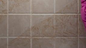 Κλείστε αυξημένος του καθαρισμού του βρώμικου τοίχου κεραμιδιών με παραδίδει το λαστιχένιο γάντι από το σφουγγάρι, εμπορικό των ο απόθεμα βίντεο
