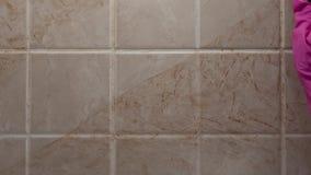 Κλείστε αυξημένος του καθαρισμού του βρώμικου τοίχου κεραμιδιών με παραδίδει το λαστιχένιο γάντι από το σφουγγάρι, εμπορικό των ο φιλμ μικρού μήκους