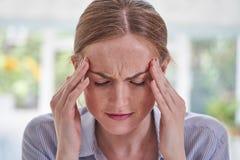 Κλείστε αυξημένος του νέου βασάνου γυναικών με τον πονοκέφαλο στοκ εικόνα