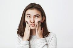 Κλείστε αυξημένος του νέου πανέμορφου brunette συμπιέζοντας το πρόσωπο με τα χέρια, ανατρέχοντας με την ανίδεη αμφισβητήσιμη έκφρ Στοκ εικόνες με δικαίωμα ελεύθερης χρήσης