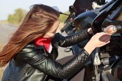 Κλείστε αυξημένος του πολυάσχολου θηλυκού motorbiker προσπαθεί να λύσει το πρόβλημα με τη σπασμένη μεταφορά, οδηγά το μοτοσυκλετι στοκ φωτογραφίες