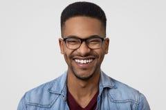 Κλείστε αυξημένος του σκοτεινού ξεφλουδισμένου τύπου με το ευρύ οδοντωτό χαμόγελο, άσπρα δόντια, φορά το πουκάμισο τζιν, θεάματα, στοκ εικόνες