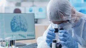 Κλείστε αυξημένος του φαρμακοποιού στη φόρμα που λειτουργεί με ένα μικροσκόπιο φιλμ μικρού μήκους