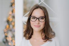 Κλείστε αυξημένος του όμορφου νέου θηλυκού προτύπου φορά τα γυαλιά για το καλό όραμα, εξετάζει ευτυχώς τη κάμερα, έχει παρακαλέσε στοκ φωτογραφίες