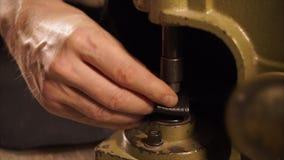 Κλείστε αυξημένος το των χεριών ατόμων ` s, το οποίο κάνει μια τρύπα σε ένα κομμάτι του δέρματος για το ντεκόρ φιλμ μικρού μήκους