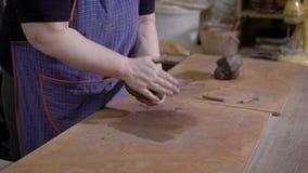Κλείστε αυξημένος το των χεριών γυναικών ` s, ο κύριος καθιστά ένα κομμάτι του αργίλου μαλακότερο και εύκαμπτο στο εργαστήριό του απόθεμα βίντεο