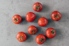 Κλείστε αυξημένος των κόκκινων ντοματών οικογενειακών κειμηλίων που στερεώνονται με τις πτώσεις του νερού στο γκρίζο κλίμα Φρέσκα στοκ φωτογραφία με δικαίωμα ελεύθερης χρήσης