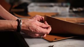 Κλείστε αυξημένος των κύριων χεριών που εργάζεται με το δέρμα και δημιουργεί τα εξαρτήματα φιλμ μικρού μήκους
