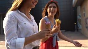 Κλείστε αυξημένος των κώνων παγωτού υπό εξέταση μιας γυναίκας που περπατά με το φίλο της Δύο νέες γυναίκες που τρώνε υπαίθρια το  απόθεμα βίντεο