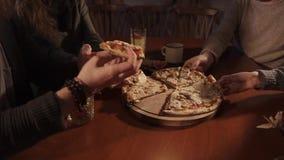 Κλείστε αυξημένος των χεριών ανθρώπων, γυναίκες ανδρών που είναι σε έναν καφέ παίρνουν μια φέτα της πίτσας απόθεμα βίντεο
