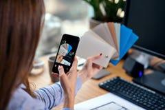 Κλείστε αυξημένος των χεριών γυναικών που παίρνουν τη φωτογραφία της παλέτας χρώματος στο σύγχρονο γραφείο πίσω όψη στοκ φωτογραφία