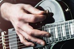 Κλείστε αυξημένος των χεριών του ατόμου που παίζει την ηλεκτρική κιθάρα στοκ εικόνα με δικαίωμα ελεύθερης χρήσης