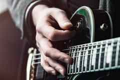 Κλείστε αυξημένος των χεριών του ατόμου που παίζει την ηλεκτρική κιθάρα στοκ φωτογραφία με δικαίωμα ελεύθερης χρήσης