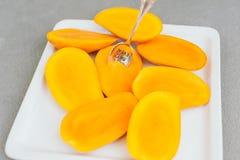 Κλείστε αυξημένος των ώριμων φετών μάγκο και του κολλημένου κουταλιού στον άσπρο δίσκο Juicy εξωτικά φρούτα Κλείστε επάνω τον ορι στοκ εικόνα με δικαίωμα ελεύθερης χρήσης