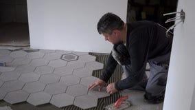 Κλείστε εξετάζει το εργάτη οικοδομών καθορίζοντας τα hexagon κεραμίδια στο τσιμενταρισμένο πάτωμα απόθεμα βίντεο