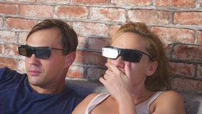 κλείστε επάνω ένα νέο ζεύγος στα γυαλιά τρισδιάστατα, καθμένος στον καναπέ στο καθιστικό με πολλές συγκινήσεις, προσέχει τον κινη απόθεμα βίντεο