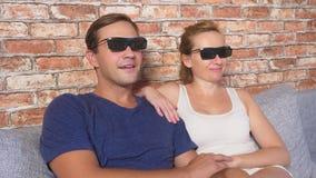 κλείστε επάνω ένα νέο ζεύγος στα γυαλιά τρισδιάστατα, καθμένος στον καναπέ στο καθιστικό με πολλές συγκινήσεις, προσέχει τον κινη φιλμ μικρού μήκους