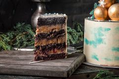 κλείστε επάνω Ένα τεμαχισμένο κομμάτι του κέικ σοκολάτας του νέου έτους βρίσκεται σε ένα ευρύ μαχαίρι σε έναν ξύλινο πίνακα Σκοτε στοκ φωτογραφία με δικαίωμα ελεύθερης χρήσης