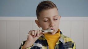 κλείστε επάνω Ένα όμορφο μικρό ξανθό αγόρι τρώει είναι νόστιμο μπισκότο σε ένα ραβδί Στο υπόβαθρο στο λευκό, στο εσωτερικό φιλμ μικρού μήκους