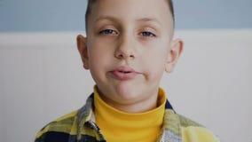 κλείστε επάνω Ένα όμορφο νέο αγόρι με τα μπλε μάτια εξετάζει τη κάμερα και κατσαρώνει τα χείλια του χαρωπά Αστείο αγόρι Στο λευκό απόθεμα βίντεο