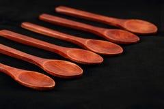 Κλείστε επάνω έξι μικρών ξύλινων κουταλιών από το σκοτεινό ξύλο σε ένα μαύρο τραπεζομάντιλο E στοκ εικόνες με δικαίωμα ελεύθερης χρήσης