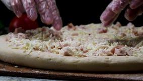 Κλείστε επάνω γιατί ο αρχιμάγειρας παραδίδει τα διαφανή γάντια σχετικά με την unbaked πίτσα στο μαύρο υπόβαθρο, που μαγειρεύει τη φιλμ μικρού μήκους