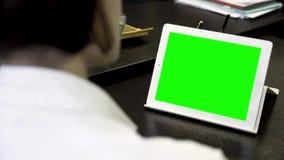 Κλείστε επάνω για μια γυναίκα που εξετάζει μια άσπρη ταμπλέτα με μια πράσινη οθόνη Κορίτσι στην άσπρη εργασία πουκάμισων στην αρχ απόθεμα βίντεο
