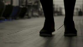 Κλείστε επάνω για τα αρσενικά πόδια που κάνουν τις ασκήσεις με το άλμα του σχοινιού, εκπαιδευτικός σκληρά στη γυμναστική r Άτομο  φιλμ μικρού μήκους