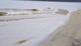 Κλείστε επάνω για τα κύματα ποταμών σε μια αμμώδη ακτή r Μικρά κύματα που πλένουν επάνω μια ακτή ποταμών με την ανοικτό καφέ άμμο απόθεμα βίντεο