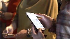 Κλείστε επάνω για τα χέρια ατόμων χρησιμοποιώντας το έξυπνο τηλέφωνο, βελτιώνοντας το επίπεδο φωτεινότητας σε ανώτατο, και δίνοντ απόθεμα βίντεο