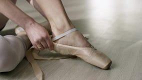 Κλείστε επάνω για την τοποθέτηση χορευτών μπαλέτου επάνω, δένοντας τα παπούτσια μπαλέτου Ballerina που βάζει στα παπούτσια pointe απόθεμα βίντεο