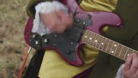 Κλείστε επάνω για το άτομο με ένα πορφυρό ηλεκτρικό παιχνίδι κιθάρων στο ντεμοντέ κοστούμι του στυλ ροκοκό τρόπου στη μαραμένη χλ φιλμ μικρού μήκους