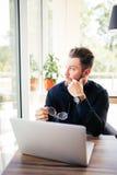 Κλείστε επάνω γυαλιών των γενειοφόρων επιχειρηματιών υπό εξέταση και της συνεδρίασης στο lap-top του και κοιτάξτε στο παράθυρο Στοκ εικόνες με δικαίωμα ελεύθερης χρήσης