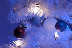 Κλείστε επάνω 5 διακοσμήσεων στο άσπρο χριστουγεννιάτικο δέντρο με το άσπρο φως στο πρώτο πλάνο και τα μπλε φω'τα στο υπόβαθρο στοκ φωτογραφίες με δικαίωμα ελεύθερης χρήσης